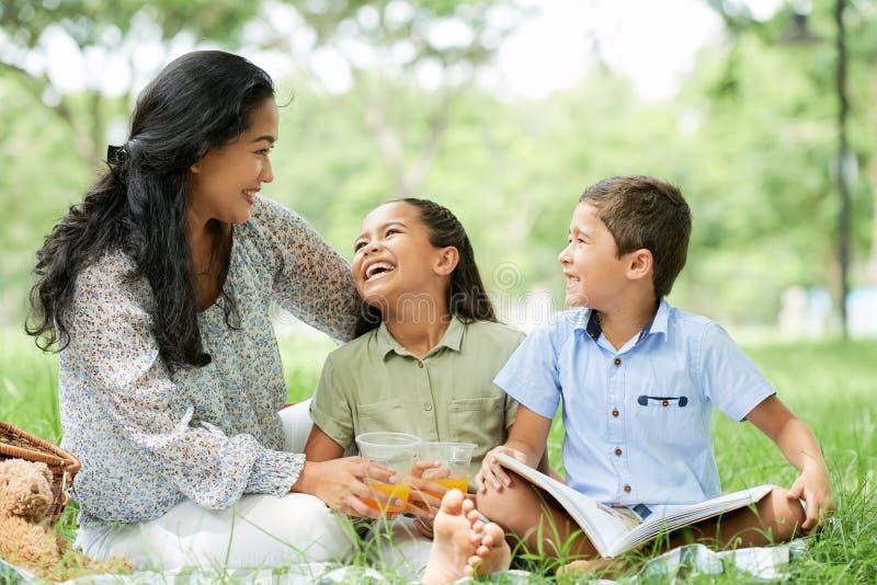 Mère et enfants asiatiques sur le pique-nique en parc photo stock