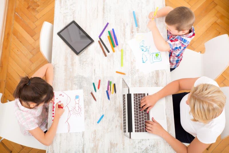 Mère et enfants avec un ordinateur portable à la maison images stock