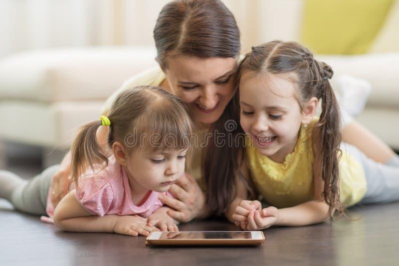 Mère et enfants heureux à l'aide du comprimé numérique sur le plancher à la maison image stock