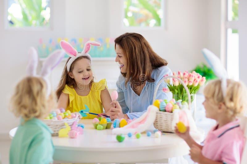 Mère et enfants, oeufs de pâques de coloration de famille photographie stock libre de droits