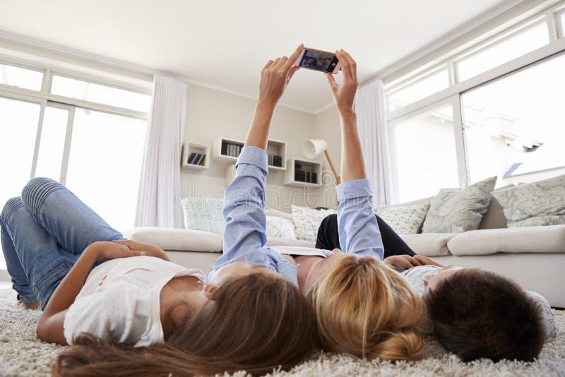 Mère et enfants se trouvant sur la couverture et posant pour Selfie à la maison photos stock