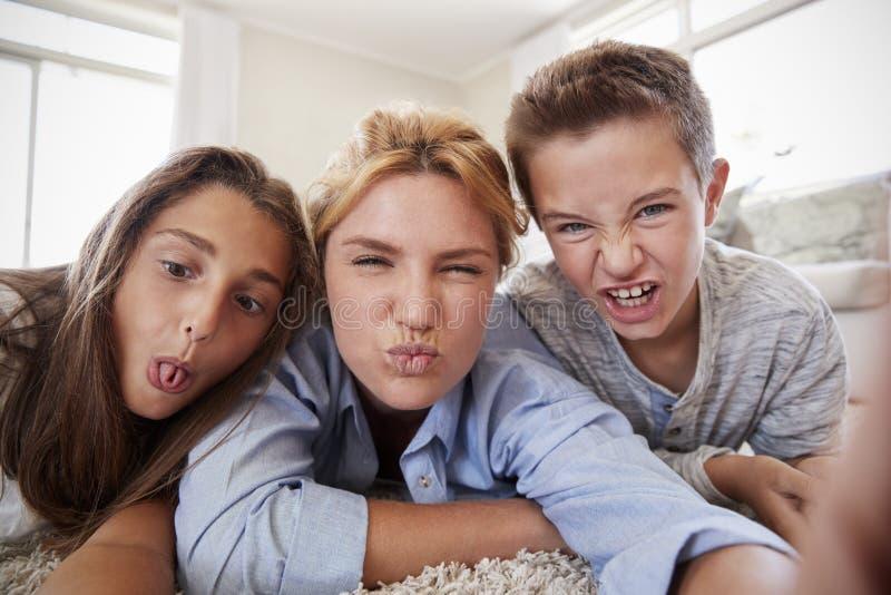 Mère et enfants se trouvant sur la couverture et posant pour Selfie à la maison photo stock