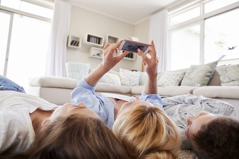 Mère et enfants se trouvant sur la couverture et posant pour Selfie à la maison photographie stock libre de droits