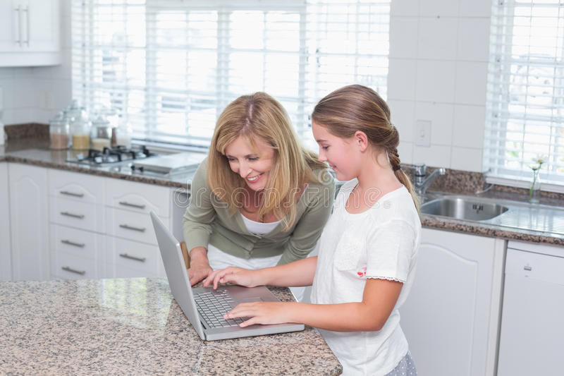 Mère et fille à l'aide de l'ordinateur portable ensemble images stock