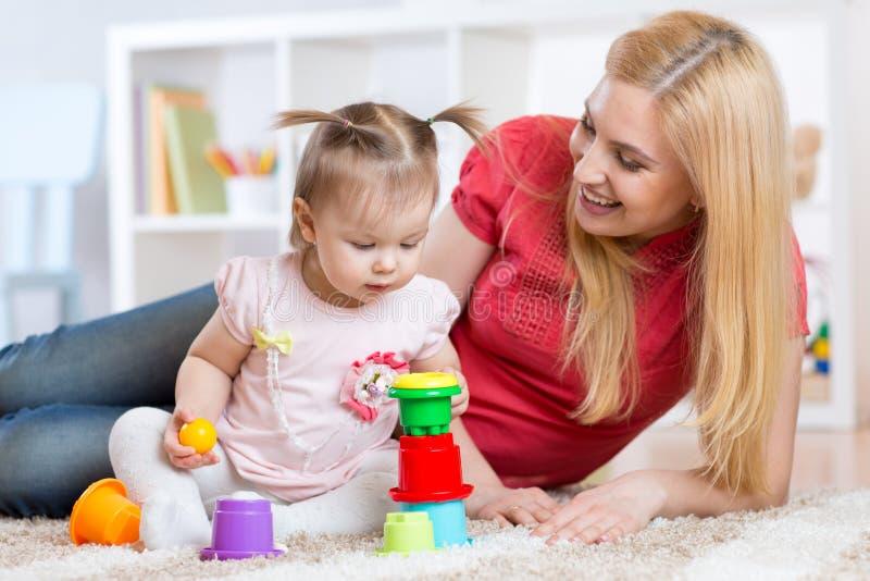 Mère et fille à l'intérieur jouant et souriant image stock