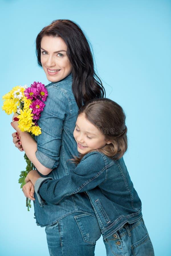 Mère et fille étreignant et tenant des fleurs dans le studio le jour bleu et heureux de mères photos stock