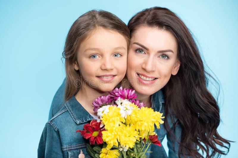 Mère et fille étreignant et tenant des fleurs dans le studio le jour bleu et heureux de mères image libre de droits