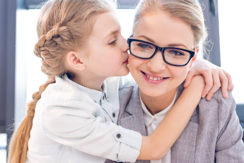 Mère et fille adorable étreignant et embrassant dans le bureau photo libre de droits
