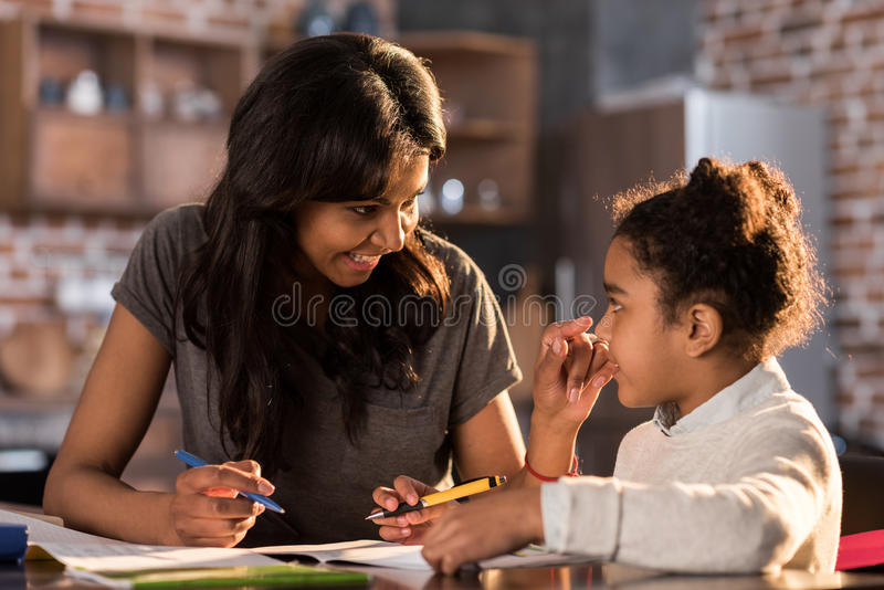 Mère et fille apprenant ensemble et faisant des devoirs, concept d'aide de devoirs photo stock