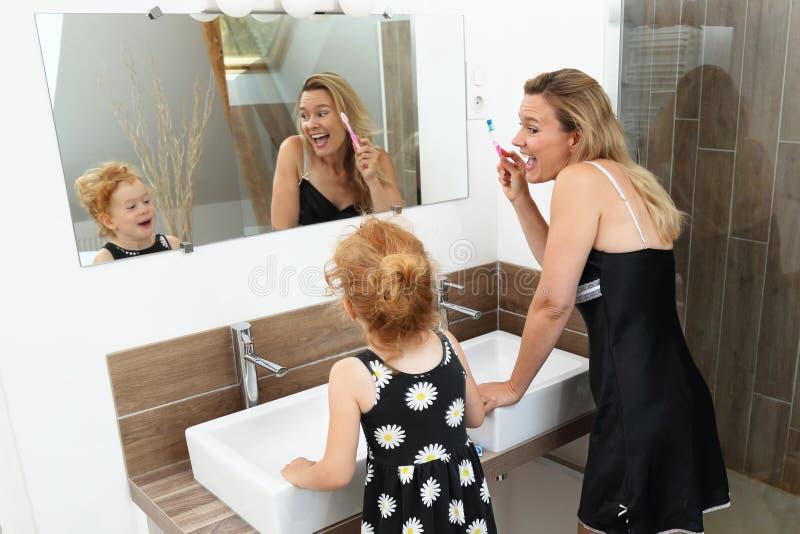 Mère et fille ayant l'amusement pendant les dents de brossage photo stock