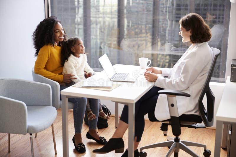 Mère et fille ayant la consultation avec le pédiatre féminin In Hospital Office image stock