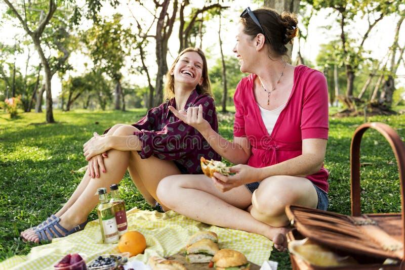 Mère et fille ayant un pique-nique dans le parc image stock