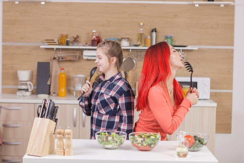 Mère et fille chantant sur des intruments de cuisine photographie stock libre de droits