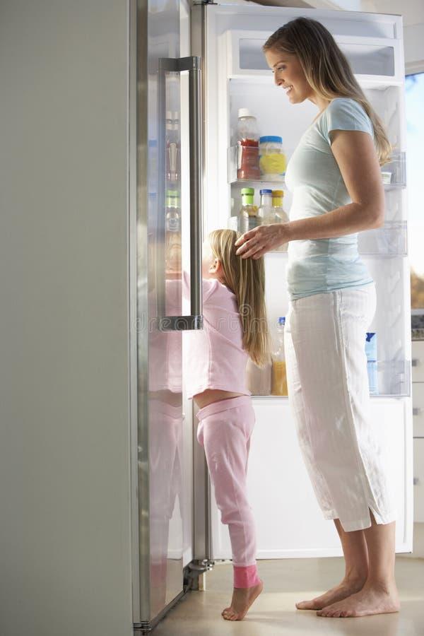 Mère et fille choisissant le casse-croûte du réfrigérateur image libre de droits