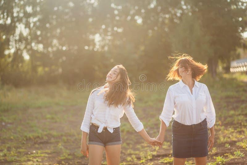Mère et fille de l'adolescence tenant des mains en été photographie stock libre de droits