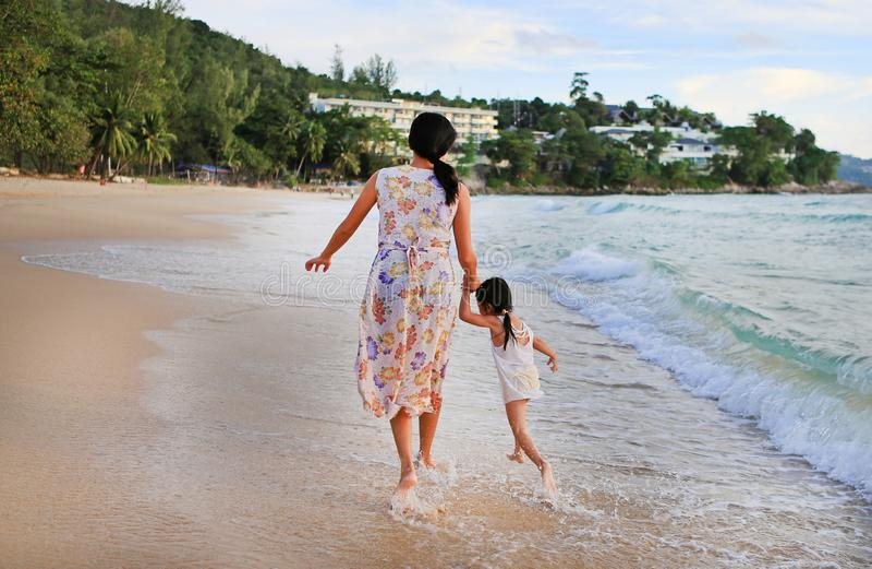Mère et fille de silhouette marchant ensemble sur la plage au coucher du soleil photographie stock libre de droits