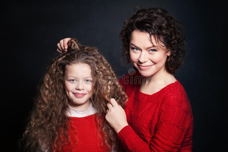 Mère et fille de sourire avec de longs cheveux bouclés image stock