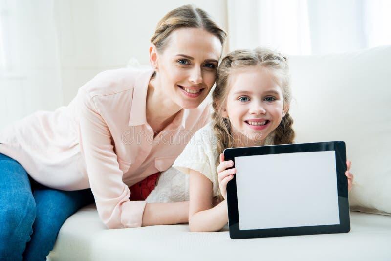 Mère et fille de sourire montrant le comprimé numérique photos stock