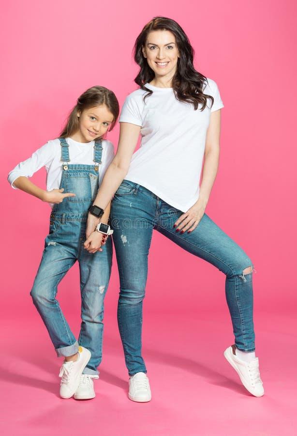 Mère et fille de sourire tenant des mains avec des smartwatches sur le rose photographie stock libre de droits