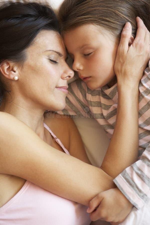 Mère et fille dormant dans le lit image libre de droits