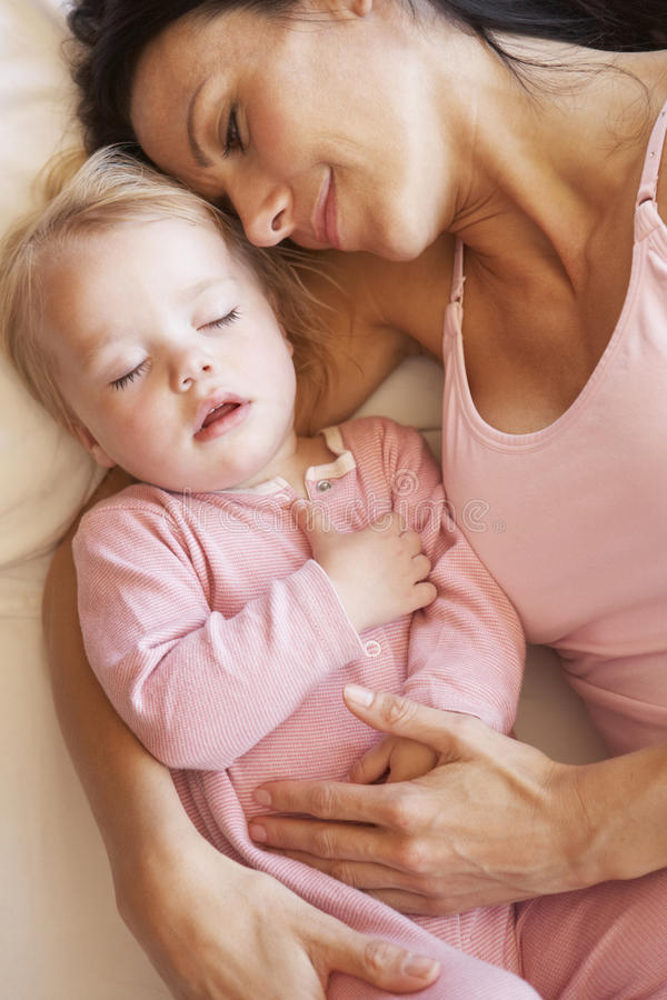Mère et fille dormant dans le lit photographie stock