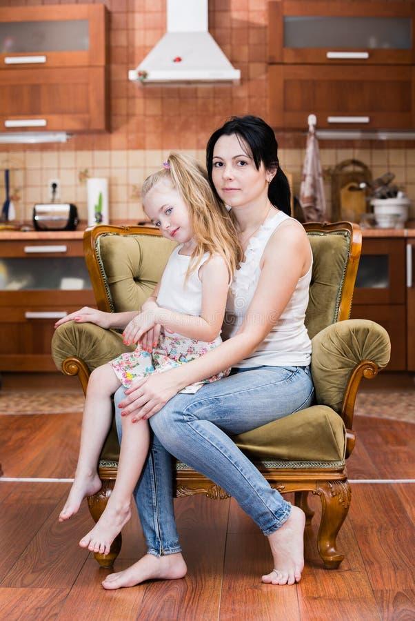 Mère et fille embrassant à l'intérieur photo stock