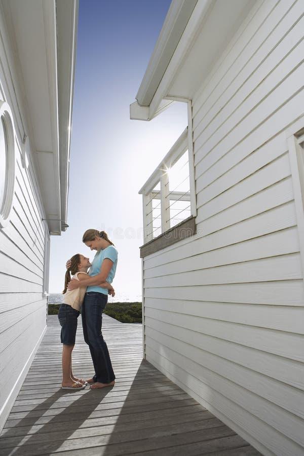 Mère et fille embrassant sur le porche photographie stock