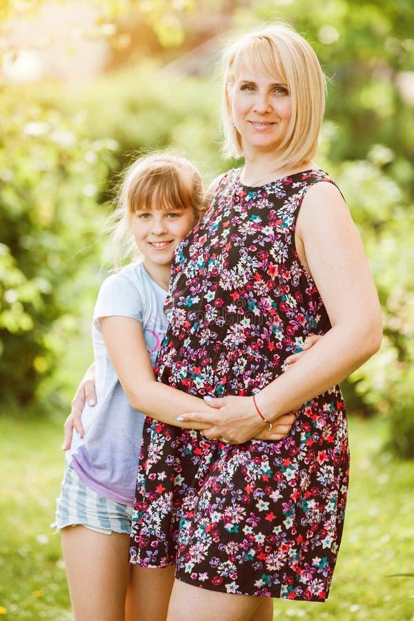 Mère et fille en parc - jeune femme enceinte et enfant regardant dans la caméra et le sourire La femme porte la robe florale photographie stock libre de droits