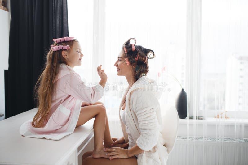 Mère et fille faisant des cheveux et le maquillage ensemble images stock