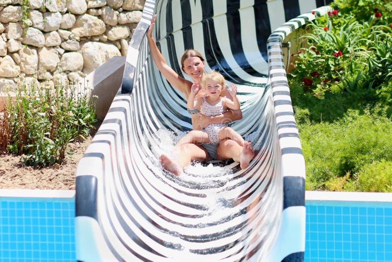 Mère et fille glissant dans l'aquapark images stock