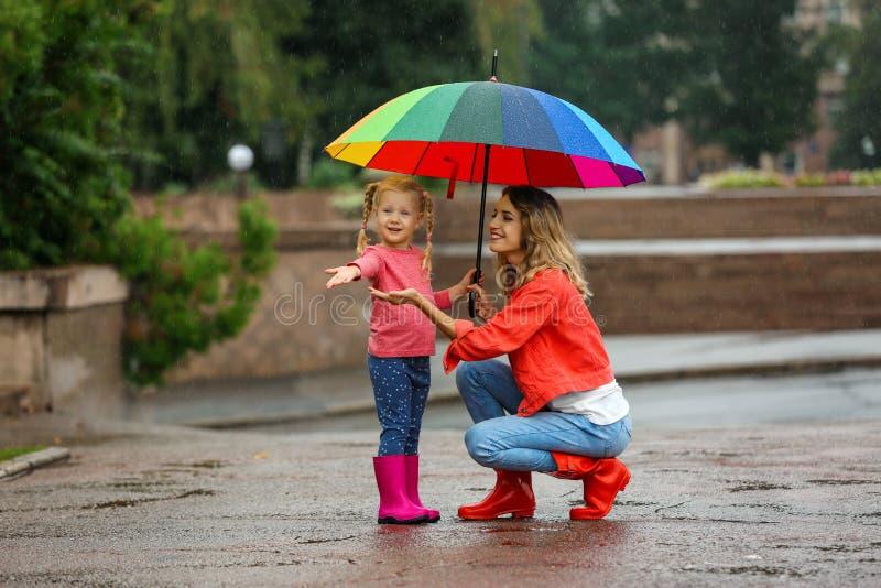 Mère et fille heureuses avec le parapluie lumineux sous la pluie photo stock