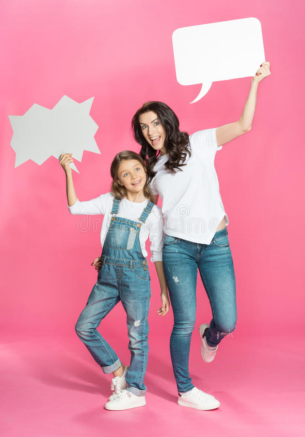 Mère et fille heureuses avec les bulles vides de la parole posant sur le rose photo stock