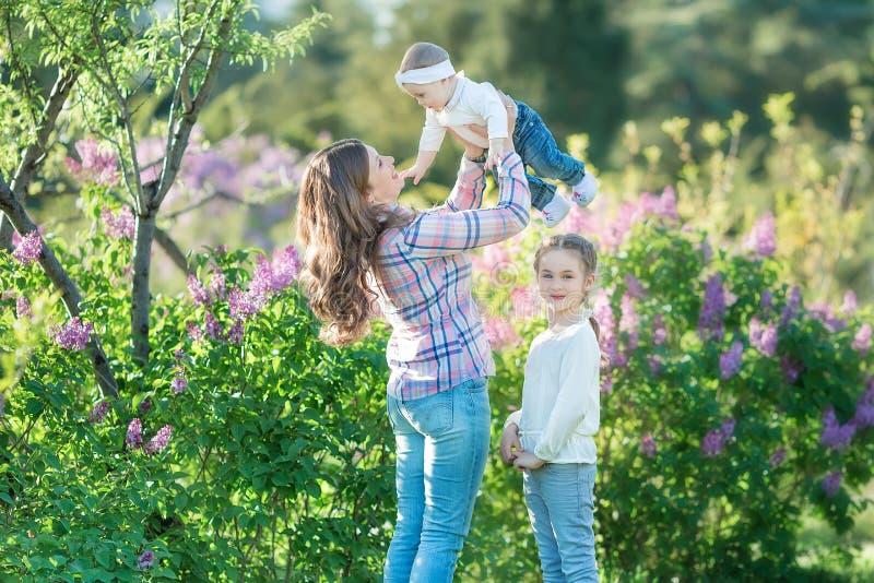 Mère et fille heureuses avec les pommes vertes dans le jardin des lilas de floraison photographie stock