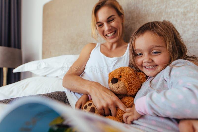 Mère et fille heureuses sur le livre de lecture de lit photo libre de droits