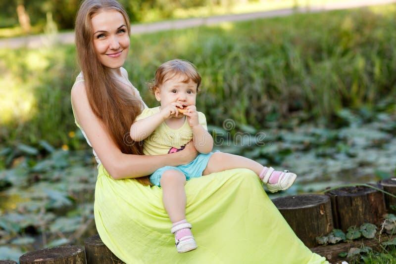 Mère et fille heureuses sur le tronçon en parc image stock