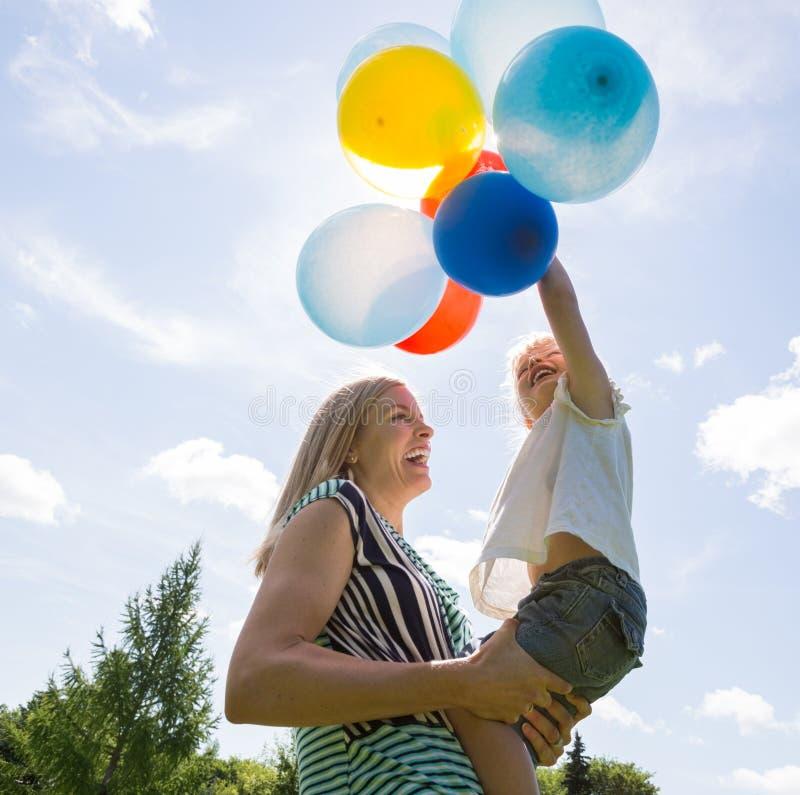 Mère et fille jouant avec des ballons contre images stock