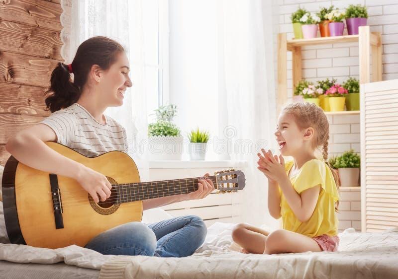 Mère et fille jouant la guitare images stock