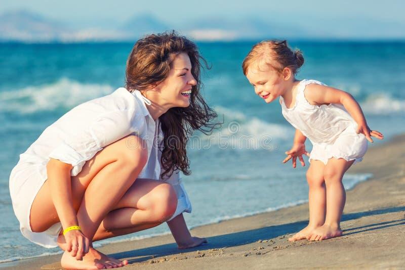 Mère et fille jouant sur la plage image libre de droits