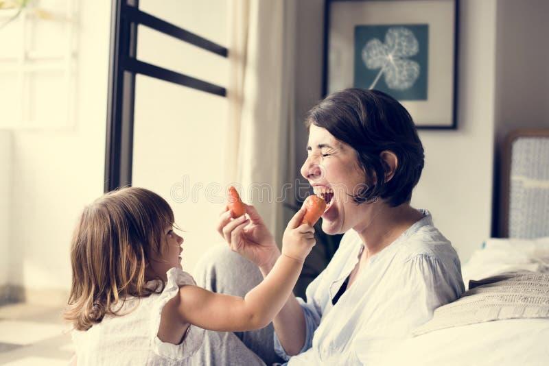 Mère et fille mangeant la carotte photographie stock