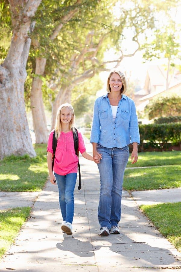 Mère et fille marchant à l'école sur la rue suburbaine photos libres de droits