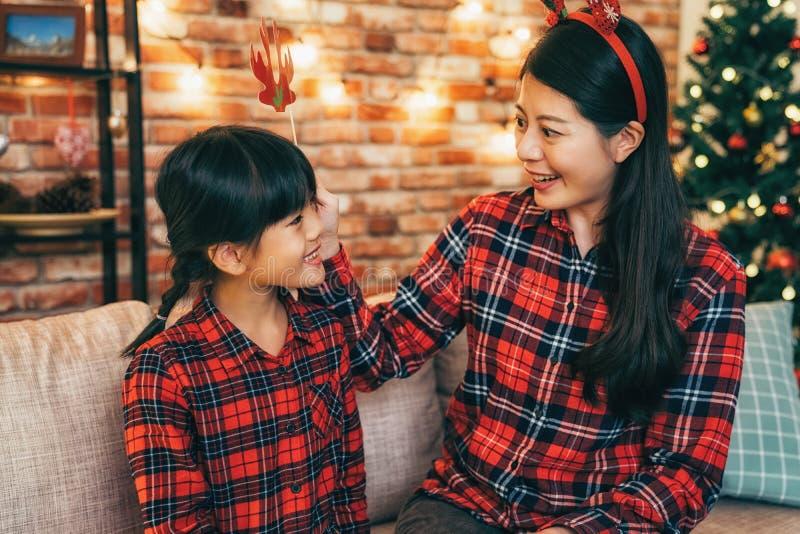 Mère et fille mignonne ayant l'amusement le réveillon de Noël photo libre de droits