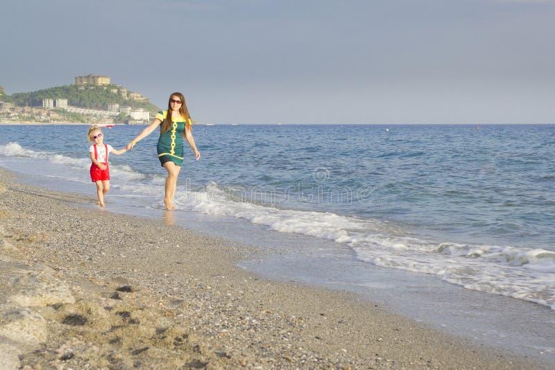 Mère et fille, promenade sur la plage photos libres de droits