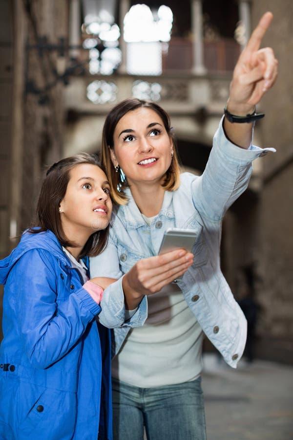 Mère et fille regardant le guide dans le téléphone photographie stock libre de droits