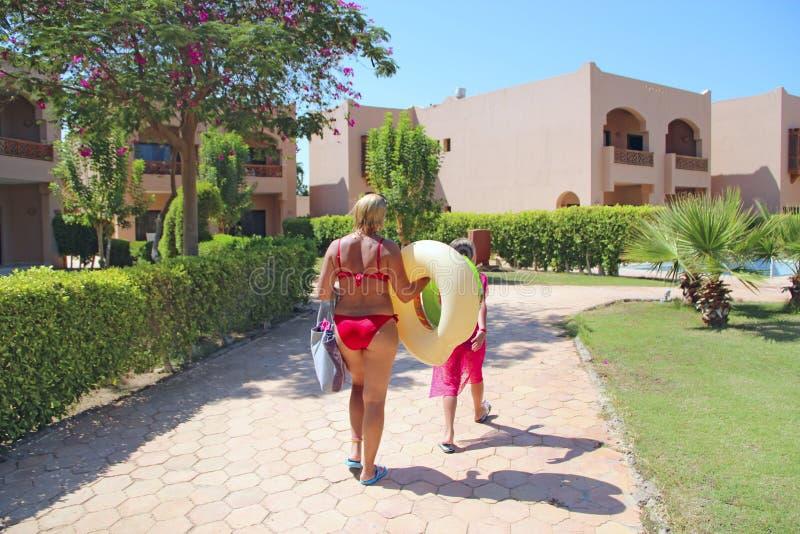 Mère et fille retournant à l'hôtel après plage Famille appréciant des vacances photos stock