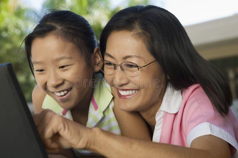 Mère et fille s'asseyant à la table d'arrière-cour utilisant la fin d'ordinateur portable ensemble  images stock