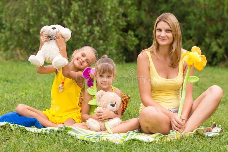 Mère et fille s'asseyant avec les jouets mous sur le pique-nique images stock