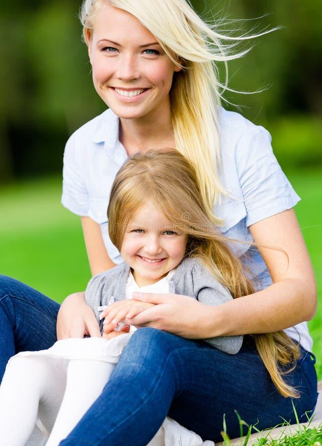 Mère et fille s'asseyant sur l'herbe verte photo stock