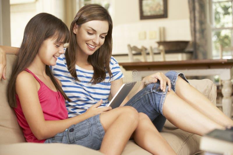 Mère et fille s'asseyant sur l'ordinateur de Sofa At Home Using Tablet images libres de droits