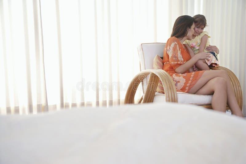Mère et fille s'asseyant sur le fauteuil image stock