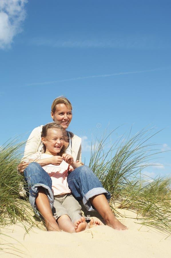 Mère et fille s'asseyant sur le sable images libres de droits
